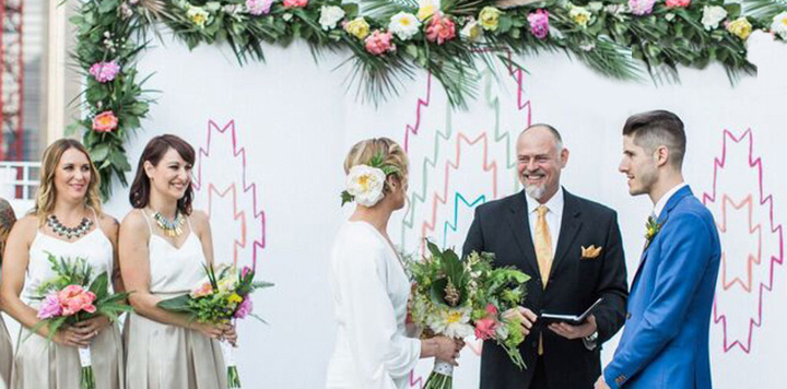 Bridesmaids with bouquets smile at wedding couple and officiant during Williamsburg Brooklyn Rooftop Wedding
