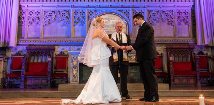 NYC Wedding Officiant Peter Boruchowitz with bride and groom holding hands in church