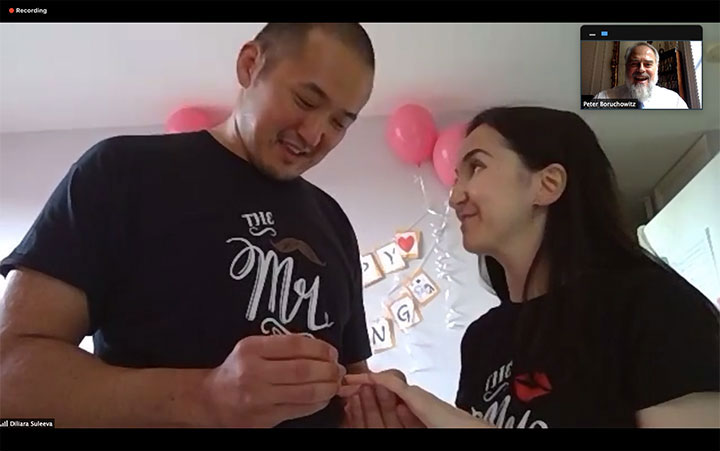 Bride and groom exchange rings during online wedding ceremony