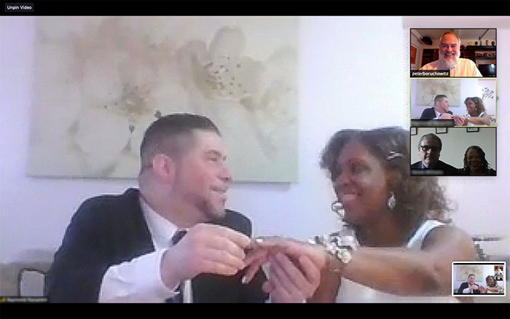 Groom places ring on brides finger during online wedding ceremony